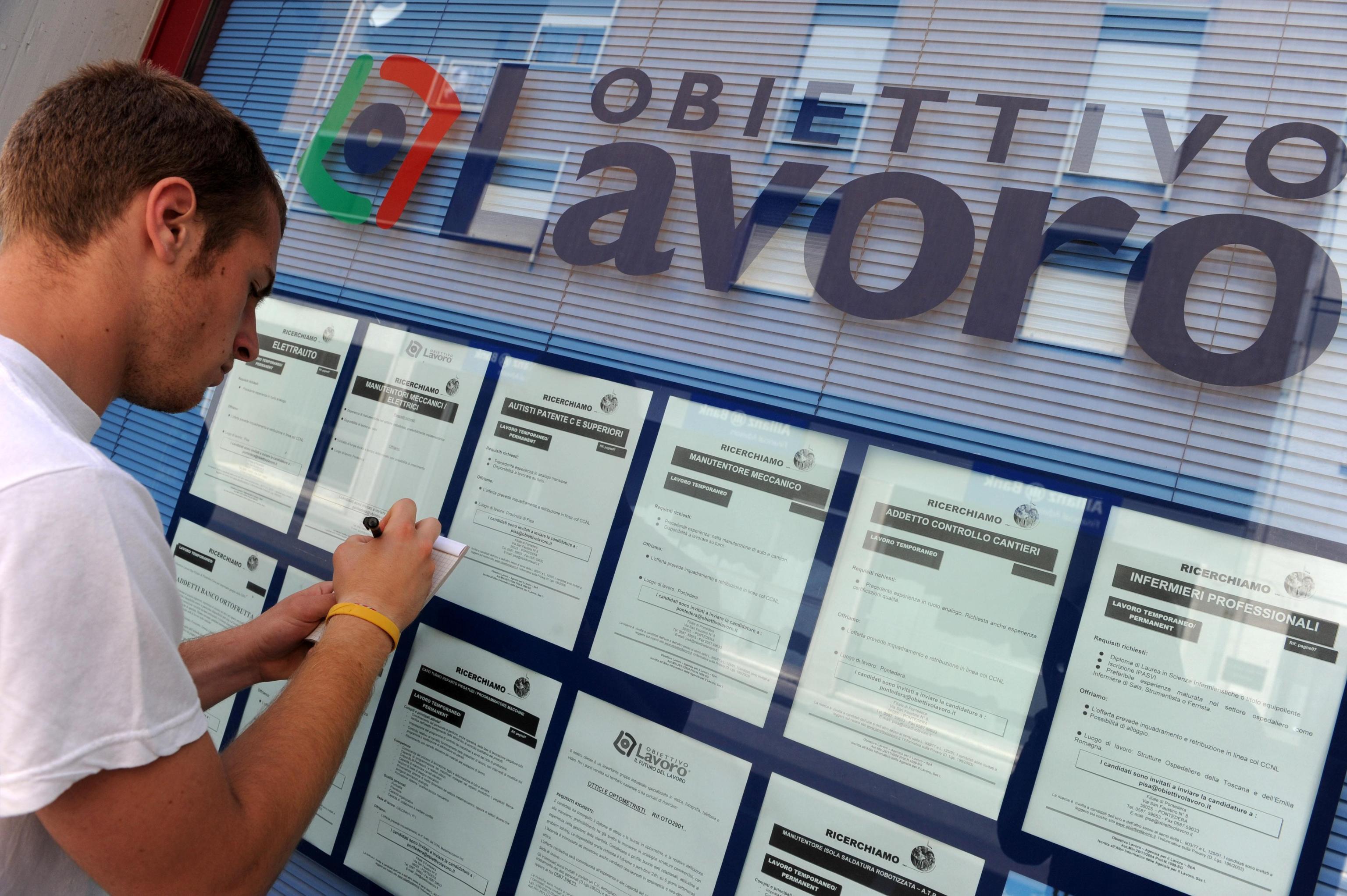Un ragazzo in cerca di lavoro davanti a una agenzia interinale,