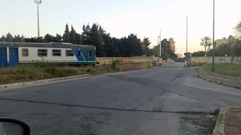 un passaggio a livello aperto all'arrivo del treno a Marsala